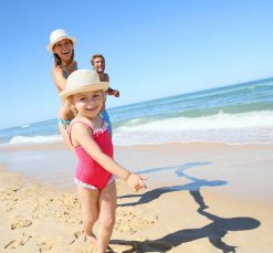 Family enjoy a day at the beach in the sun